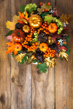 Thanksgiving front door wreath with pumpkins and autumn leaves. Fall greeting background with seasonal berries and cones, copy space