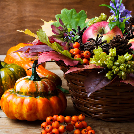 Thanksgiving table centerpiece with apples and autumn leaves in wicker basket, close up. Fall greeting background Stock Photo