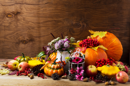 Thanksgiving arrangement with pumpkins, rowan berries, clower, birdcage decorated cones and pink flower, copy space