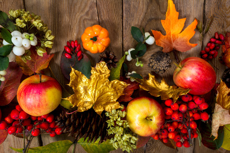 Thanksgiving greeting with apples, rowan, golden maple leaves and seeds on the rustic wooden background