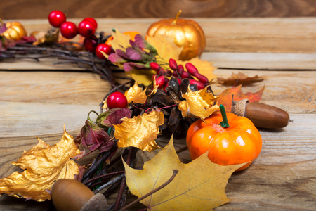 Fall background with pumpkins, red berries, golden and yellow maple leaves on the wooden table