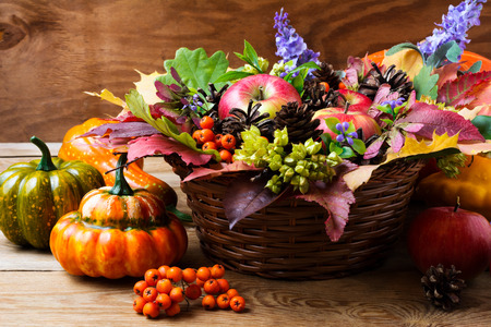 Thanksgiving wicker basket table centerpiece with squash and autumn leaves. Fall greeting background Stock Photo
