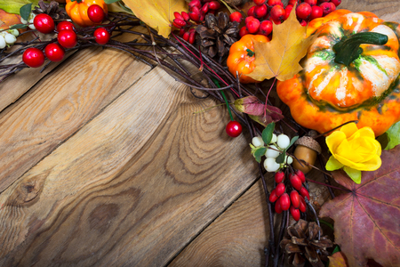 Fall background with decorative pumpkin, red berries and yellow rose on the wooden table, copy space