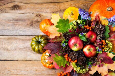 cuerno de la abundancia: Thanksgiving decoration with pumpkin, apples, green oak leaves, blue flowers, cones. Fall greeting background, copy space