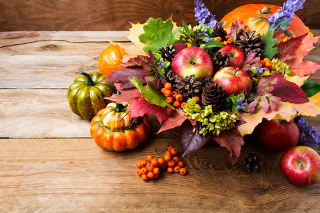 Thanksgiving or fall greeting background with ripe apples, rowan berries, green seeds, blue flowers, pumpkins, leaves