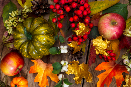 Thanksgiving greeting with green pumpkin, apples, rowan, white berries, golden and orange maple leaves on the rustic background
