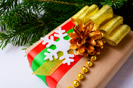 Christmas gift box with felt snowflake, golden ribbon, pine cone and beads