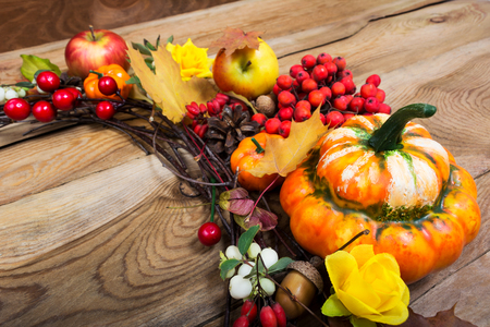 Fall background with decorative pumpkin and red berries on the old wooden table, copy space