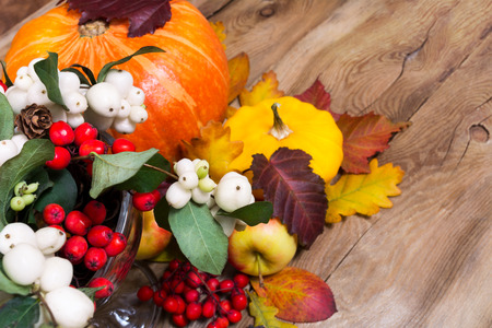 Thanksgiving or fall background with snowberry and rowan berries, pumpkin, apples, cones and yellow squash