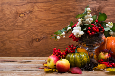 Fall table centerpiece with snowberry and rowan berries, green pumpkin, apples, cones on the rustic wooden background, copy space Фото со стока