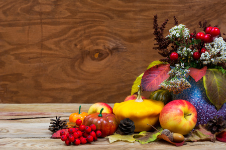 Fall arrangement with red berries, white flowers and leaves in purple vase, pumpkins, apples, cones, copy space Stock Photo