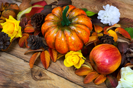 Thanksgiving orange pumpkin, apple, pine cones and yellow roses wreath on the wooden background, close up