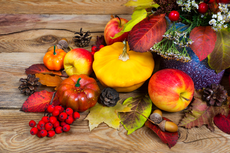 Fall arrangement with red berries, white flowers and leaves in purple vase, yellow squash, apples, cones, close up Stock Photo