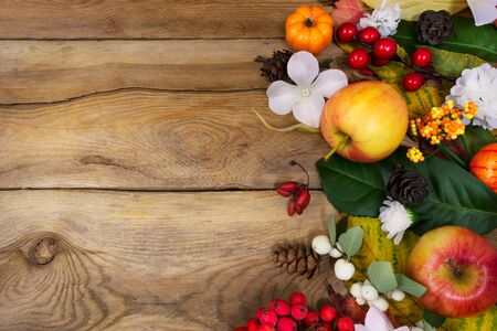 Thanksgiving or fall greeting background with pumpkin, apples, green and yellow autumn leaves and white flowers on the rustic wooden table, copy space