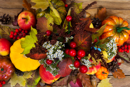 Fall arrangement with white flowers, red berries, colorful leaves, pumpkins, apples, cones, acorns on the rustic wooden background, top view