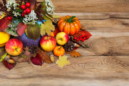 Thanksgiving table centerpiece with white flowers in vase, pumpkins, apples, cones, acorns and colorful fall leaves, copy space