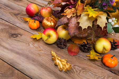 Thanksgiving arrangement with apples, golden pumpkin, maple and oak leaves on the rustic wooden background, copy space Stock Photo