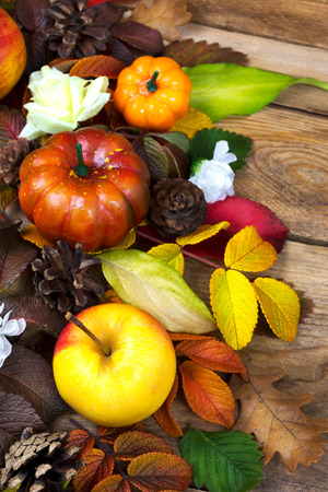 Thanksgiving decoration with apple, pumpkin, pine cones and colorful fall leaves on the rustic wooden background