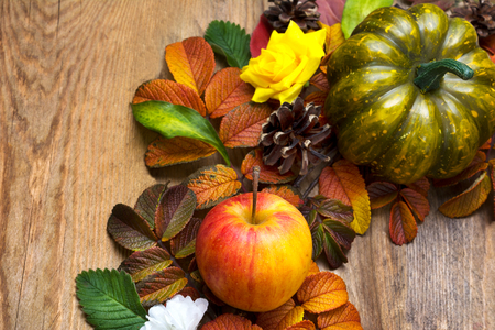 Fall wreath with green pumpkin, ripe apple, yellow silk roses and leaves on the wooden background, top view Stock Photo