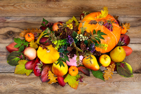cuerno de la abundancia: Thanksgiving or fall arrangement with wild flowers in the pink vase, pumpkins, apples, pears and colorful fall leaves on the wooden background, top view