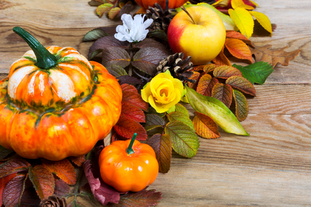 Thanksgiving decoration with pumpkins, apples, leaves and silk flowers on the rustic wooden background