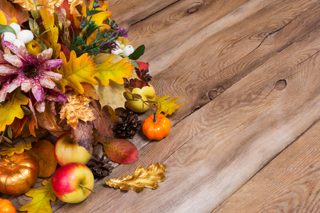 Rustic fall background with silk flowers, apples, golden pumpkin and oak leaves, copy space