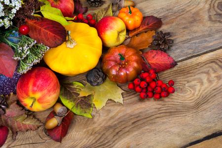 ローワンの果実、白い花、黄色のスカッシュ、りんご、コーン、ドングリ、コピースペースと感謝祭のアレンジ