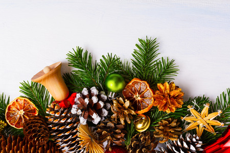 Christmas greeting background with cones, wooden and golden jingle bells, copy space.