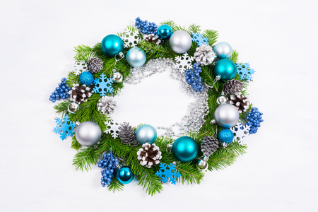 Christmas silver, blue, turquoise baubles, felt snowflakes and pine cones wreath on the white background Stock Photo