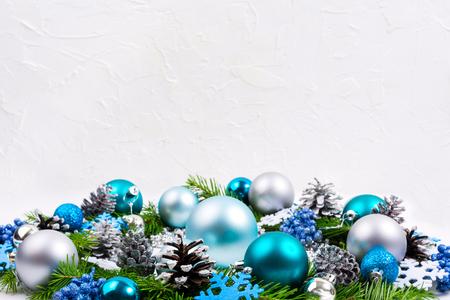 Saludo navideño con adornos de plata, azul pálido, turquesa, copos de nieve, bayas de glitter y conos de pino en el fondo blanco, copia espacio.