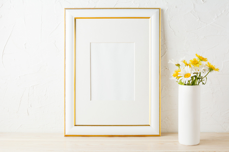 Gold decorated frame mockup with white and yellow daisy wildflowers in the cylinder vase. Empty frame mock up for presentation artwork. Template framing for modern art.