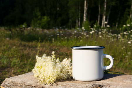 Campfire enamel coffee mug mockup with white wild flowers on the old timber.  Empty mug mock up for design promotion.