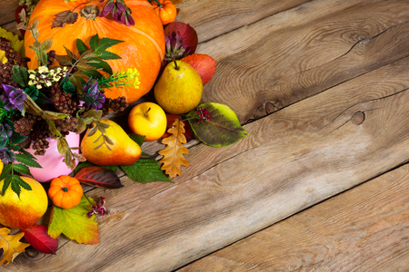 Thanksgiving background with ripe pumpkin, apples, pears and fall leaves on the rustic wooden table, copy space