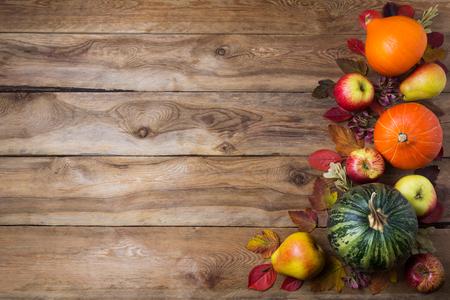 Thanksgiving decor with green pumpkin, orange onion squash, fall  leaves, apples and pears on the rustic wooden background, copy space