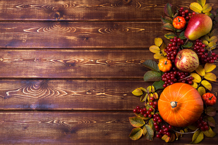 Thanksgiving frame with orange pumpkins, fall rosehip leaves, apple, pear and viburnum berries on the rustic wooden background, copy space