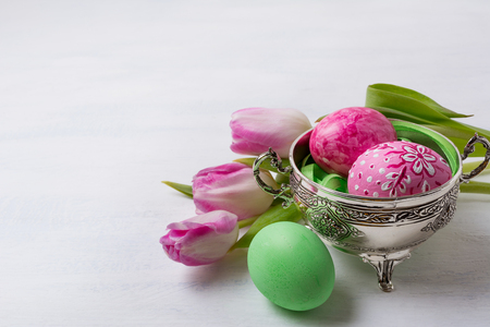 Happy Easter greeting card with pink floral painted eggs in the metal bowl, green egg and tulips, copy space.