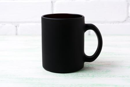 Black coffee mug mockup with white painted brick wall. Empty mug mock up for brand promotion.