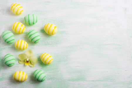 Easter background with green striped painted eggs and yellow orchid. Happy Easter greeting card, copy space.