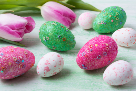 Happy Easter greeting background with tulips and white, green, pink glitter and stars decorated eggs.