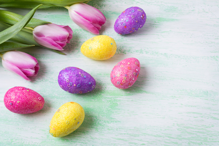 Easter background with white, pink, purple, yellow glitter and stars decorated eggs and tulips. Happy Easter greeting card, copy space.