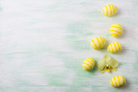 Easter background with yellow striped painted eggs and orchid. Happy Easter greeting card, copy space.