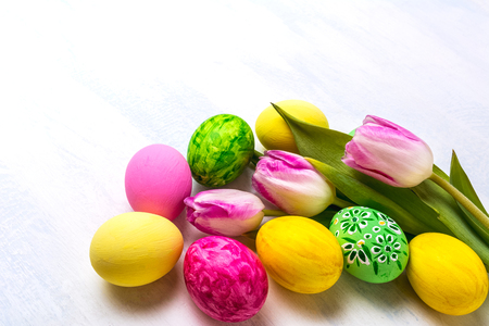 Easter green, yellow, pink painted eggs and tulips. Happy Easter greeting card or invitation, copy space