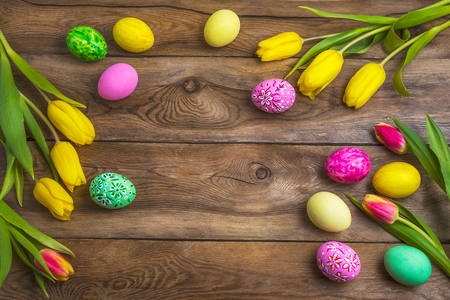 Easter rustic wooden background with pink, yellow and green painted eggs and tulips. Happy Easter greeting card, copy space. Imagens