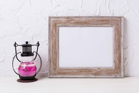 Rustic wooden landscape frame mockup with black pink metal candle lantern. Empty frame mock up for presentation design. Template framing for modern art.