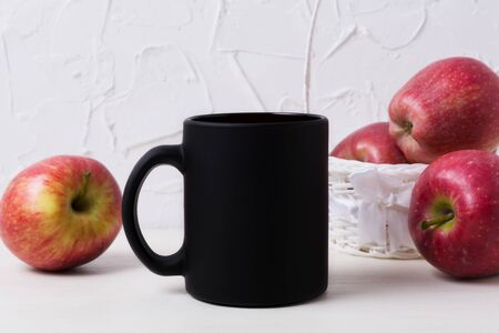 Black coffee mug mockup with with red apples in the white wicker basket. Empty mug mock up for brand promotion.