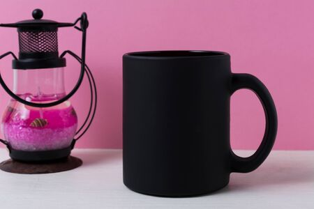 Black coffee mug mockup with metal candle lantern on the pink background. Empty mug mock up for brand promotion.