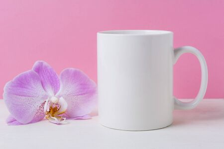 White coffee mug mockup on the pink background with purple orchid. Empty mug mock up for design promotion.