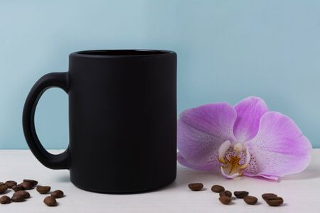 Black coffee mug mockup with purple orchid and coffee beans. Empty mug mock up for brand promotion.