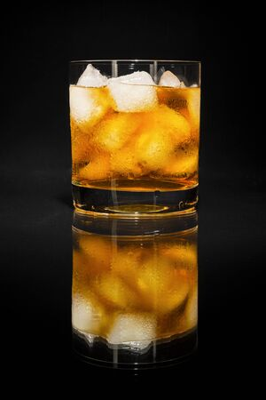 Old fashioned whiskey scotch glass on the black background.