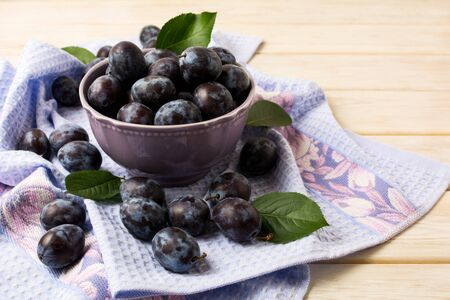 Ceramic bowl with fresh plums and blue rustic napkin on the white wooden table